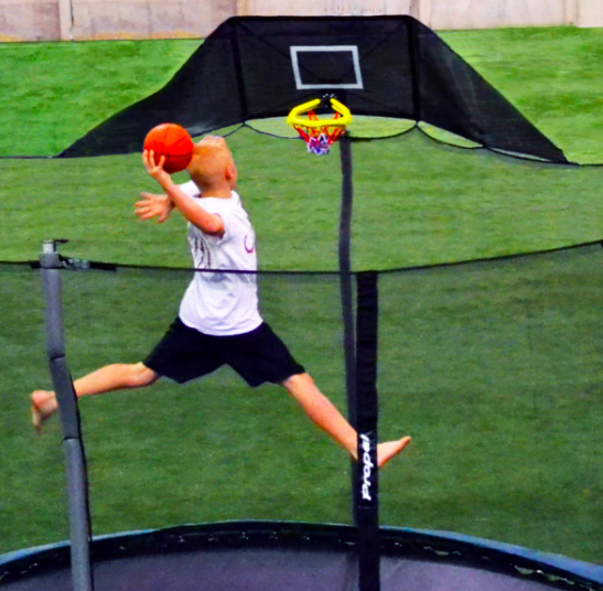 A child dunking a basketball on a trampoline.