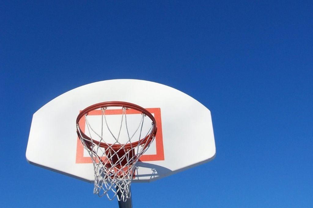 A basketball hoop against a blue sky.