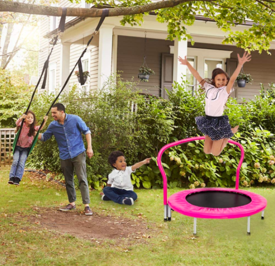 Little girl jumps on the Binrrio Kids Trampoline while a toddler looks on.