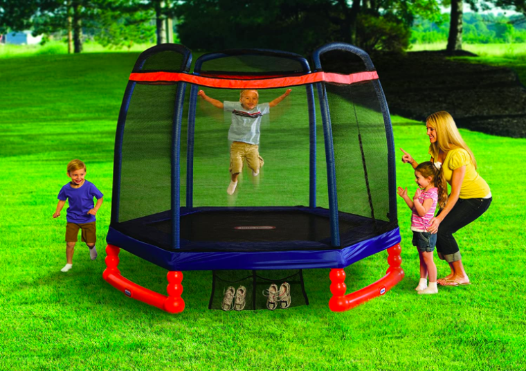 Little Tikes 7' Trampoline with young child bouncing and mom looking on with another child.