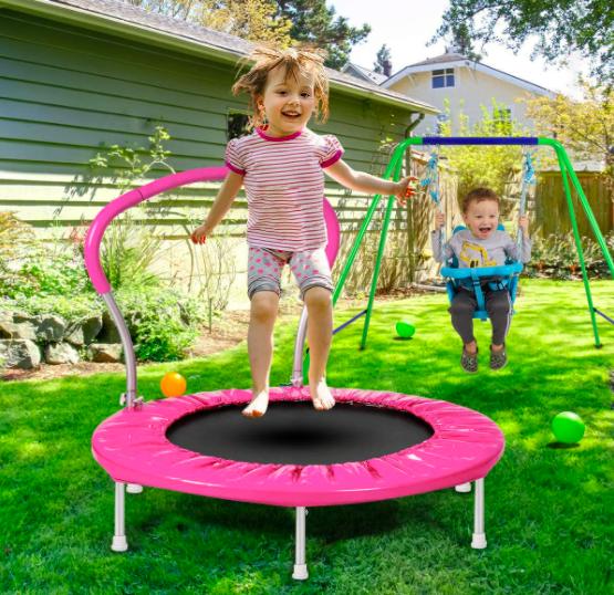 Little girl jumping on toddler trampoline. Little boy swinging on the swingset
