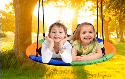 Two children smile while laying on their new tree swing, the WV Wonder View Tree Swing.