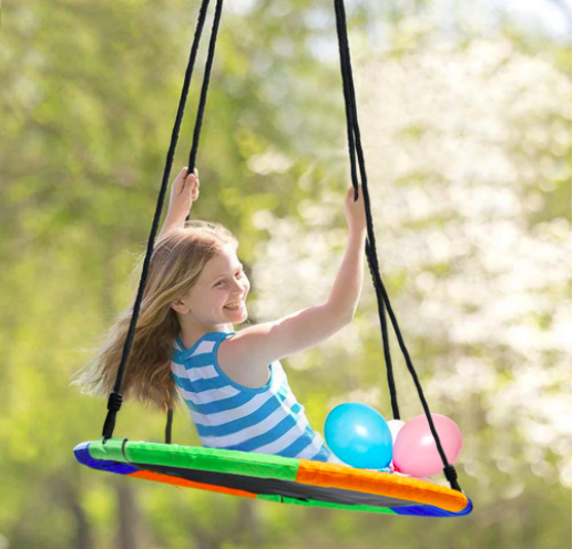 Young girl smiles while playing on the swing.