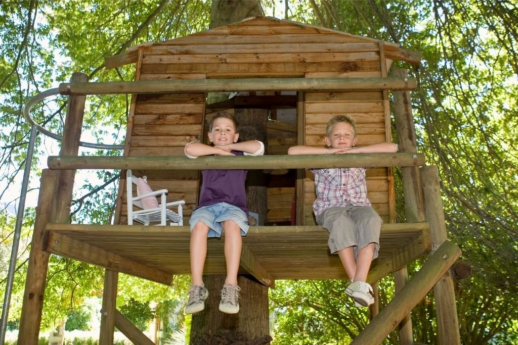 Two boys admire their work as they sit atop their treehouse
