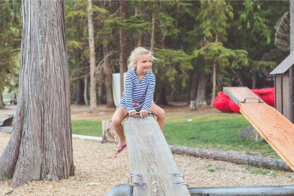 Young girl at the top of a teeter totter in her backyard.