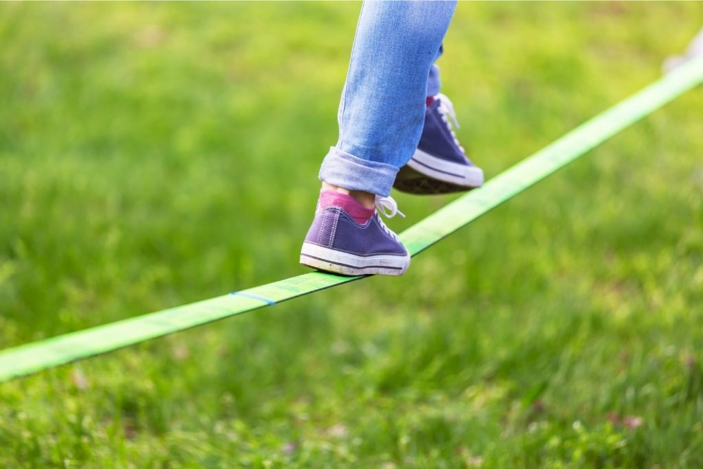 Balance is key when it comes to slacklining. Slacklining is one of the best backyard ideas for kids.