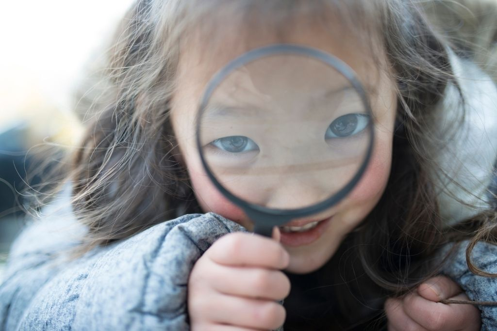 Little girl looks through a magnifying glass into the camera.