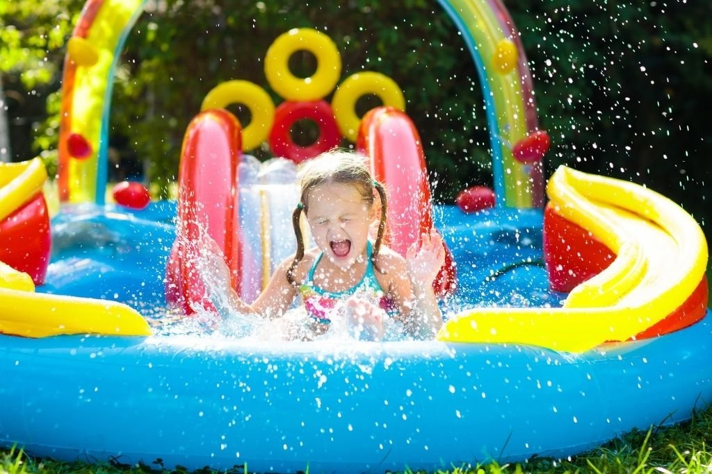 Young girl smiles as she splashes into the pool from her water slide. One of the best backyard ideas for kids.