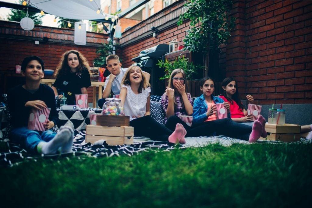 Neighborhood friends sit and enjoy a summer movie in the backyard.