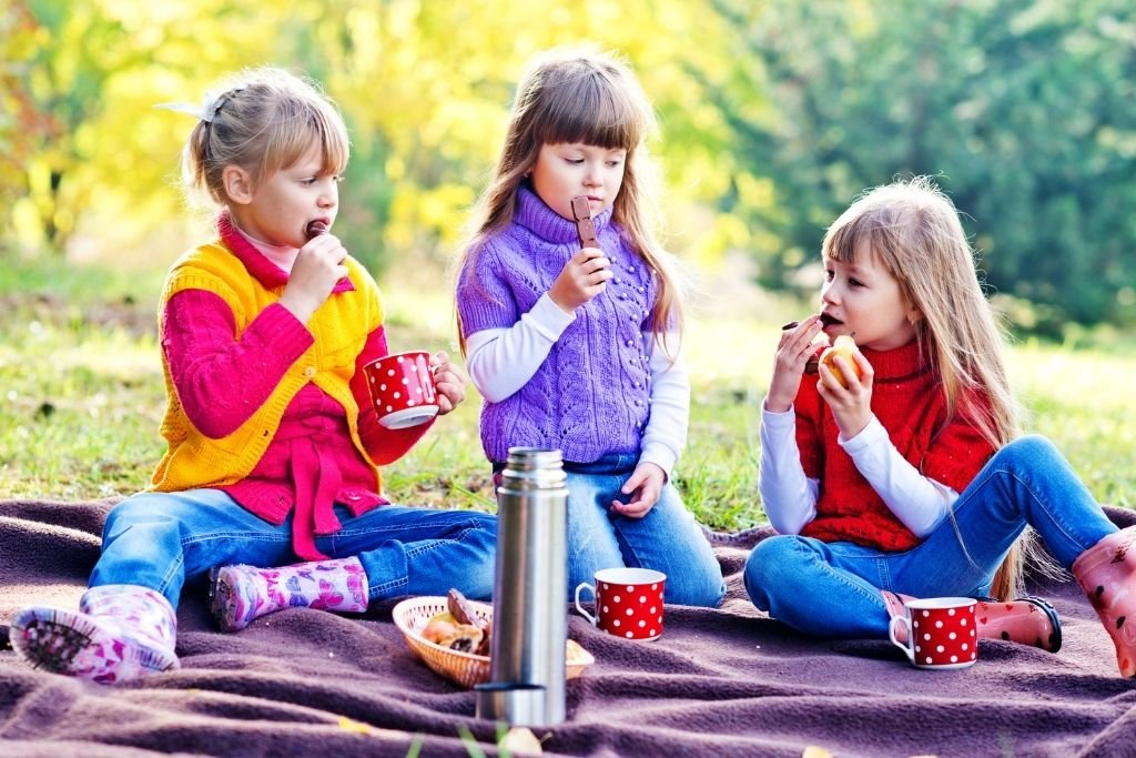 Kids enjoying a nice picnic on a gorgeous fall day. Picnics are one of the best backyard ideas for kids.