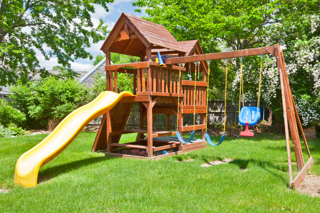 Swing set with yellow slide and blue swing.