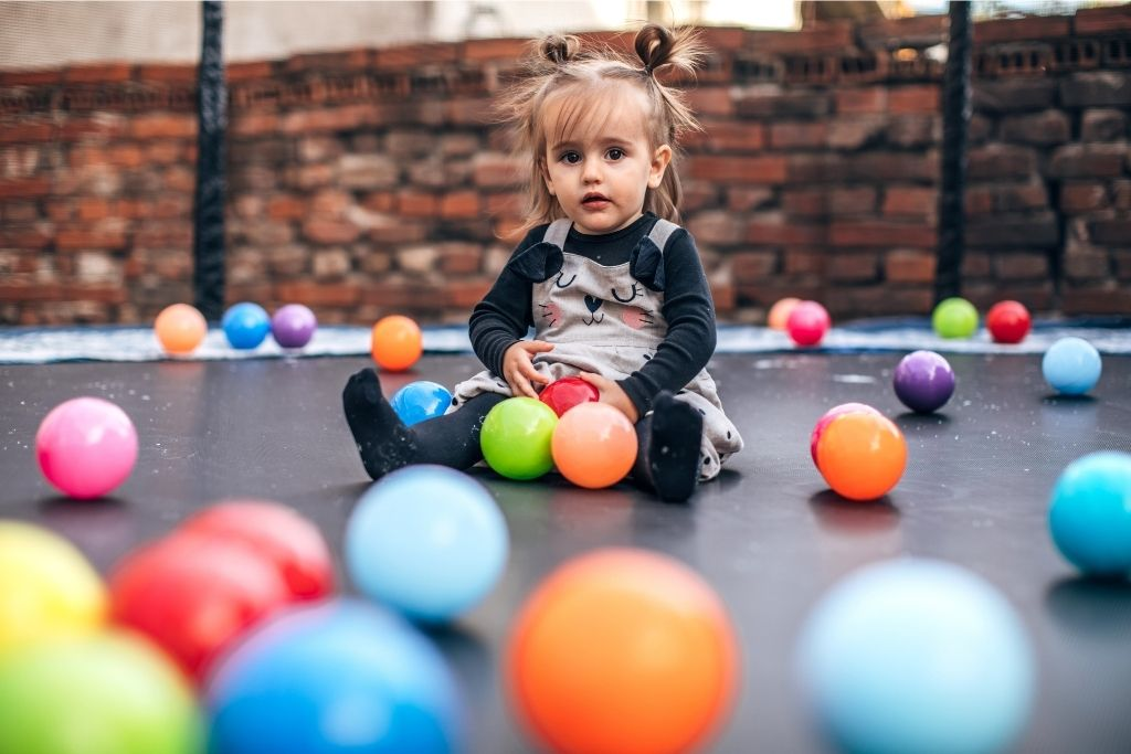 Little Toddler Sits On Trampoline and Plays With Ball Pit Balls