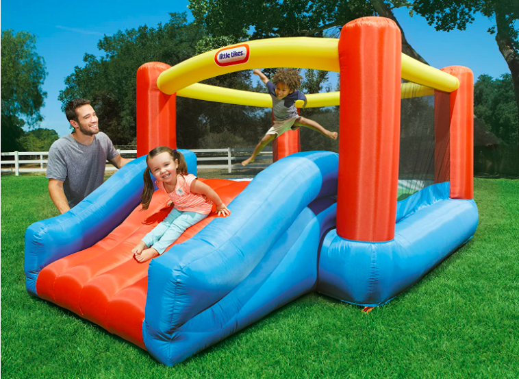 A father and two young children playing on a toddler bounce house