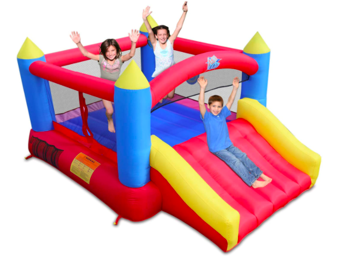 Three kids playing on a bounce house.