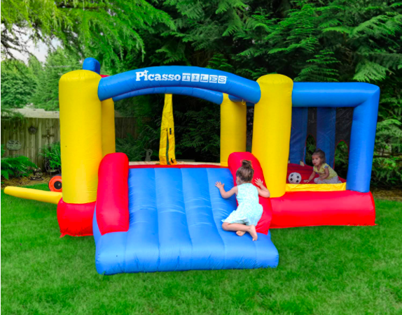 A backyard with a colorful toddler bounce house with slide and ball pit.