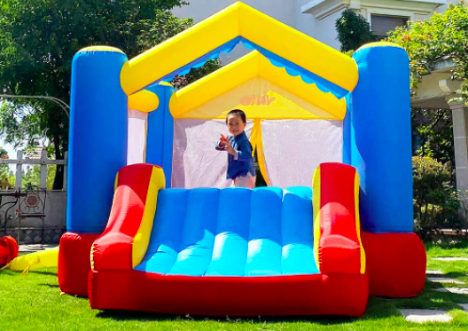 Toddler Plays In Big Bounce House With Double Slide