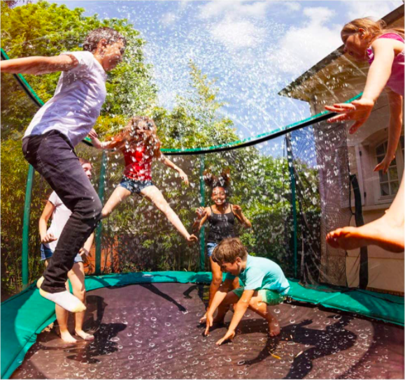 Many kids jumping on a trampoline with this sprinkler.