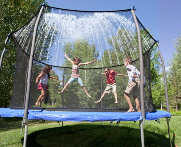 Four children jumping and playing on a trampoline with a sprinkler.