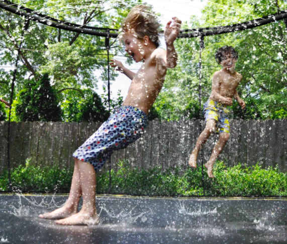 Two boys jumping and splashing on a trampoline.