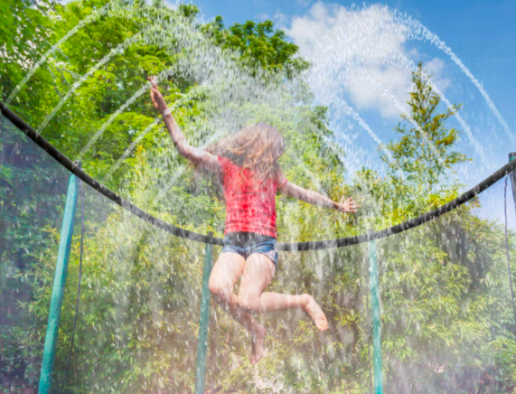 Young girl jumping around on a trampoline while being sprayed with a sprinkler.
