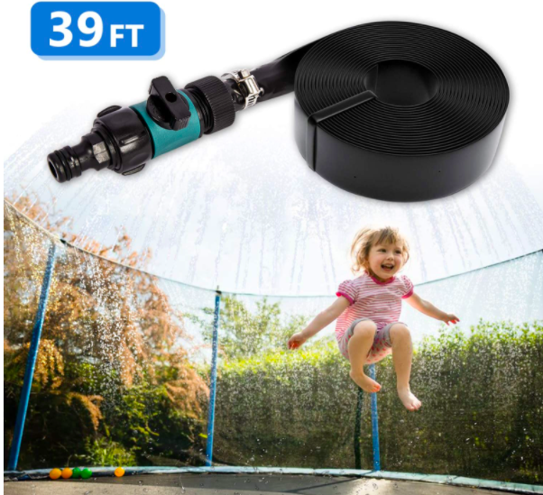 A young girl jumping on a trampoline and being sprayed by a sprinkler