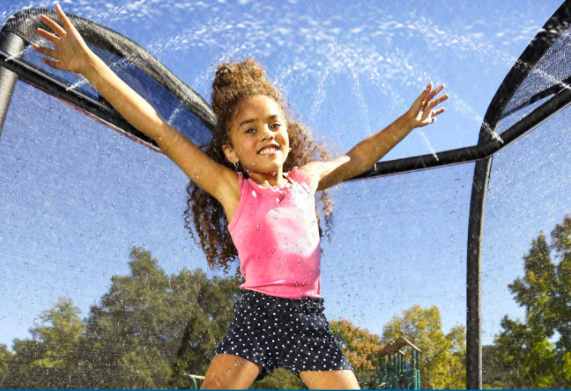 Young girl jumping on a trampoline with a sprinkler.