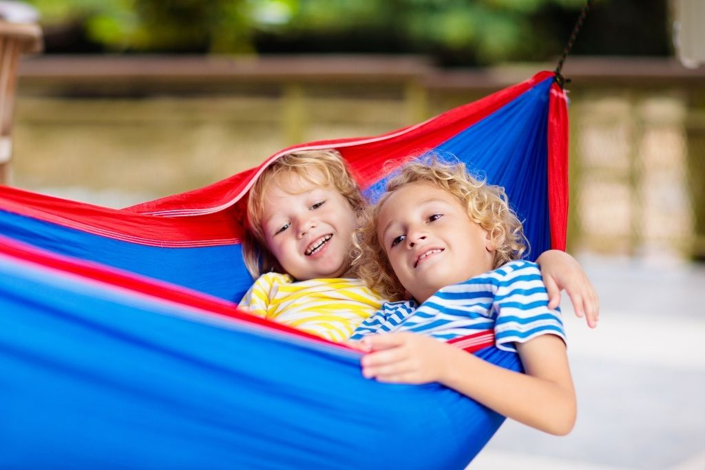 Two children in a hammock smiling