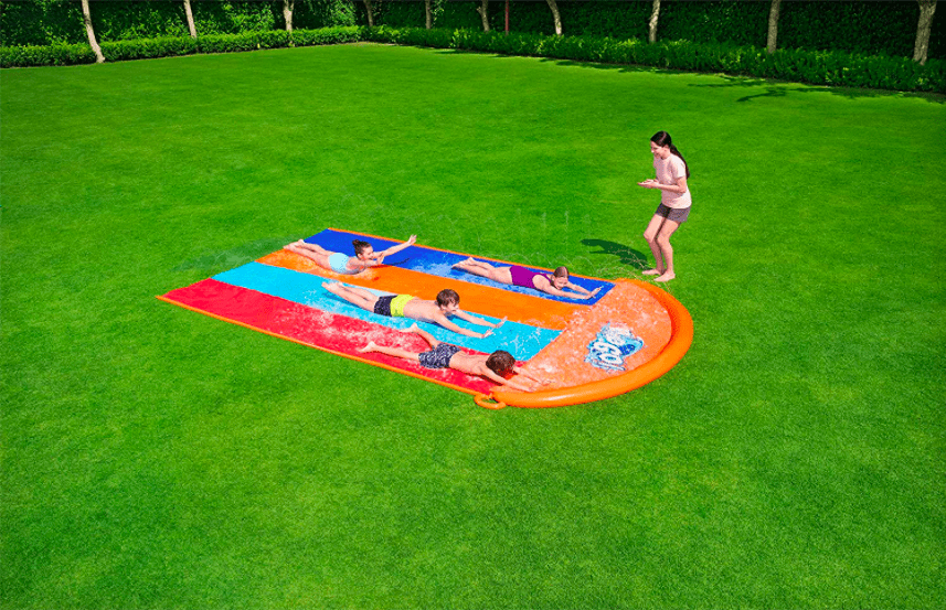 Four children playing on a backyard slip and slide