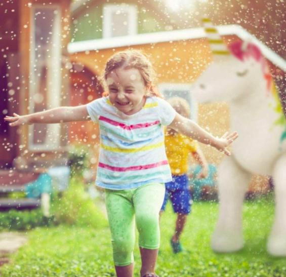 A Young Girl Running Through The Jasonwell Unicorn Sprinkler