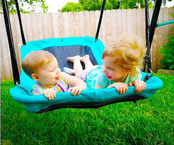 Two Young Toddlers Swinging On A Swing Set.