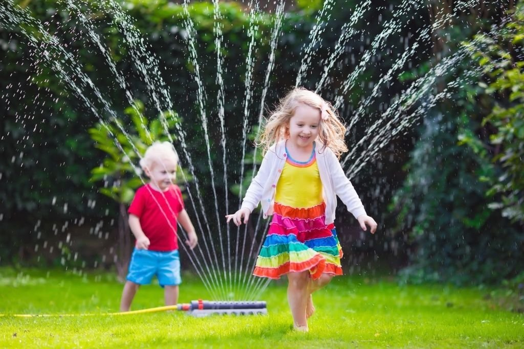 Toddlers playing with a sprinkler.