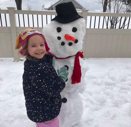 Little Girl Standing Proudly Next To Her Decorated Snowman From Her Decorating Snowman Kit.