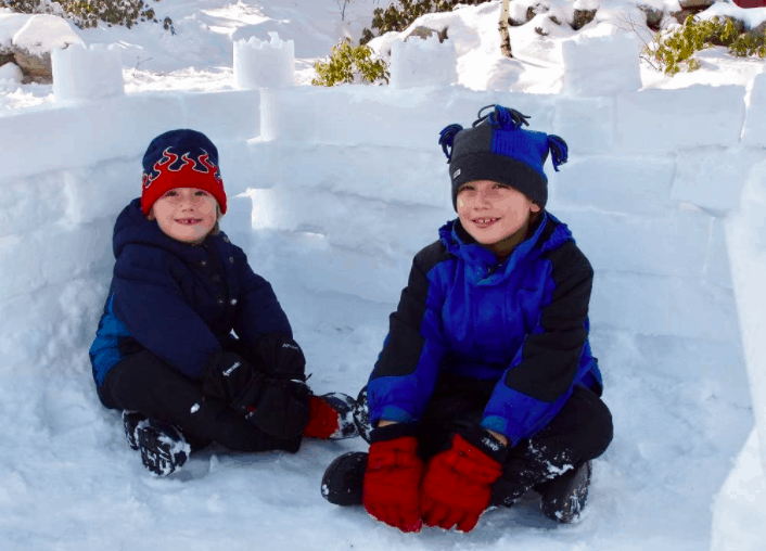 Two Boys Sitting In An Igloo Outside During Winter.