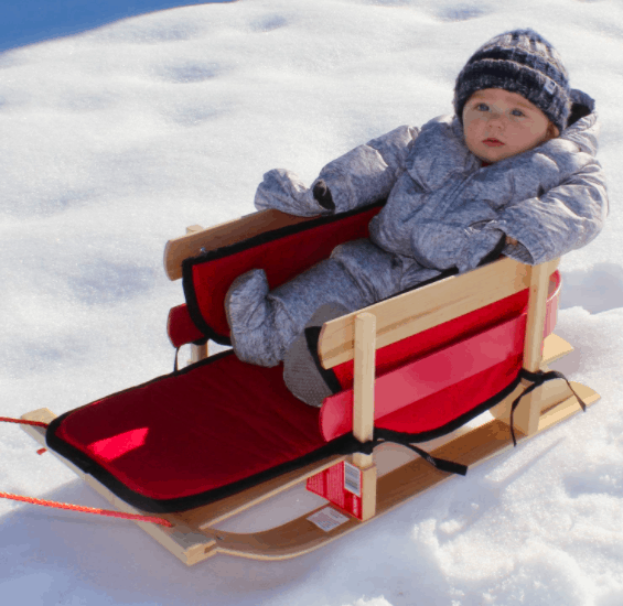 Little Girl Sitting In A Riding Winter Sleigh, One of The Best Outdoor Winter Toys For Kids.
