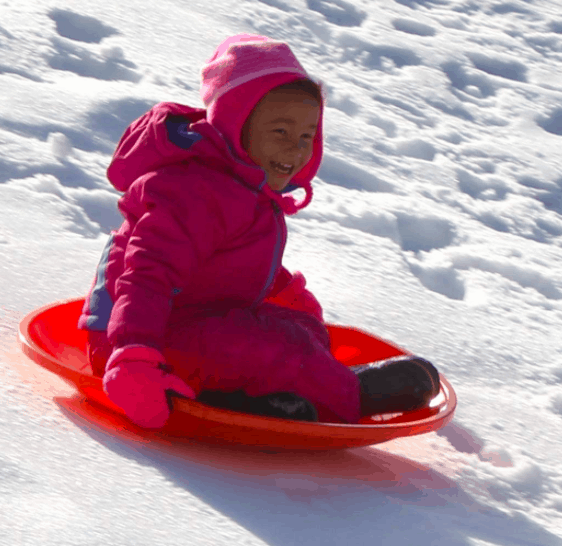 A Little Girl Riding Down A Snowy Hill in A Red Saucer Sled, An Excellent Outdoor Winter Toy For Kids.