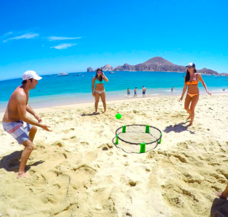 People playing spikeball on the beach.