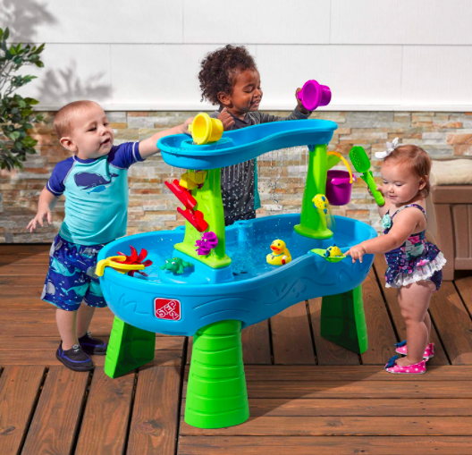 Three Children Playing with A Water Table on a Deck.