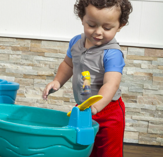 A Little Boy Playing With A Toy Attached To His Water Table.