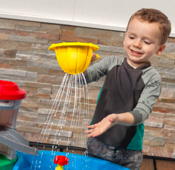 A Little Boy Playing With A Yellow Strainer That Comes With His Paw Patrol Water Table.