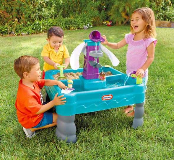 Three Young Kids Playing With A Water And Sand Table.