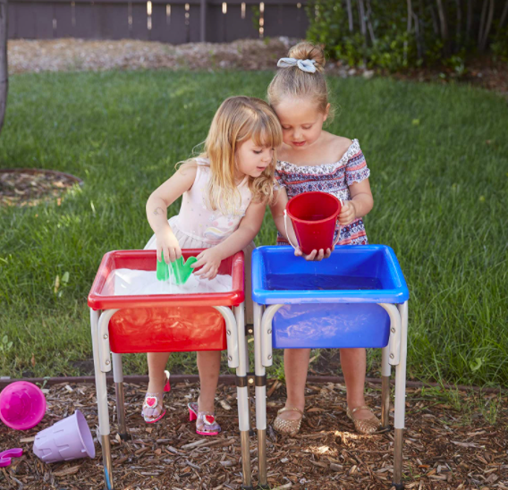 Two Young Girls Playing With The Steel Water Table.
