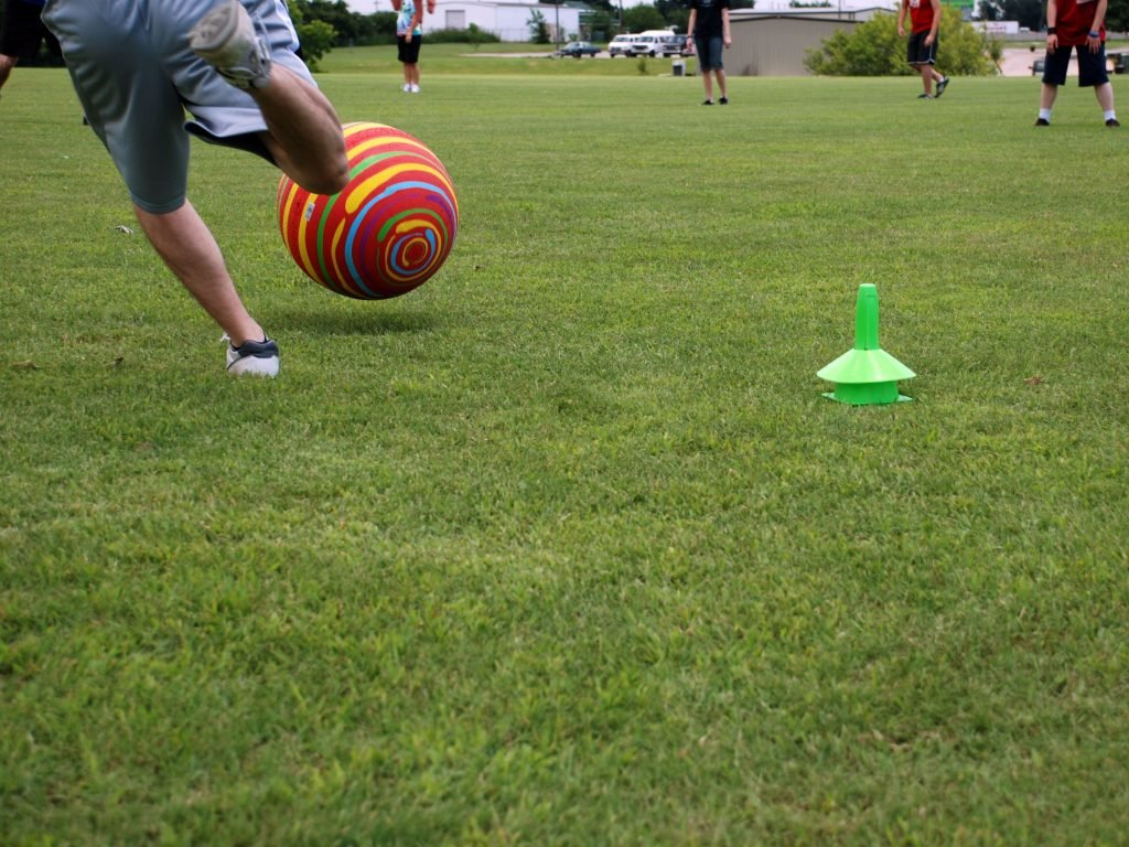A game of kickball. The batter is kicking the ball to the outfield. Kickball is one of the most entertaining backyard games for kids.