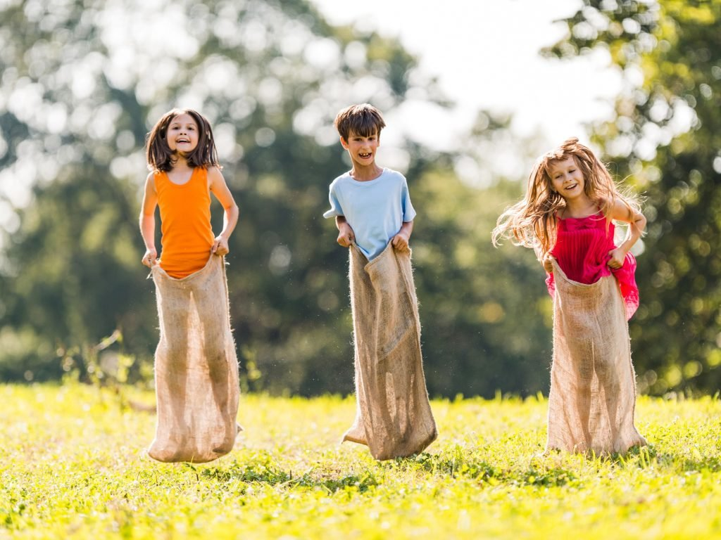 Three children in gunny sacks hopping in the grass. A sack race is a great game for entertaining the kids in your backyard this summer.