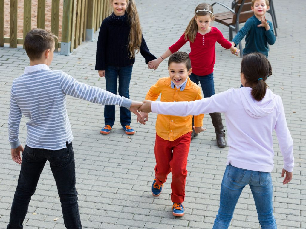 A young boy running toward the opposite team while playing Red Rover.