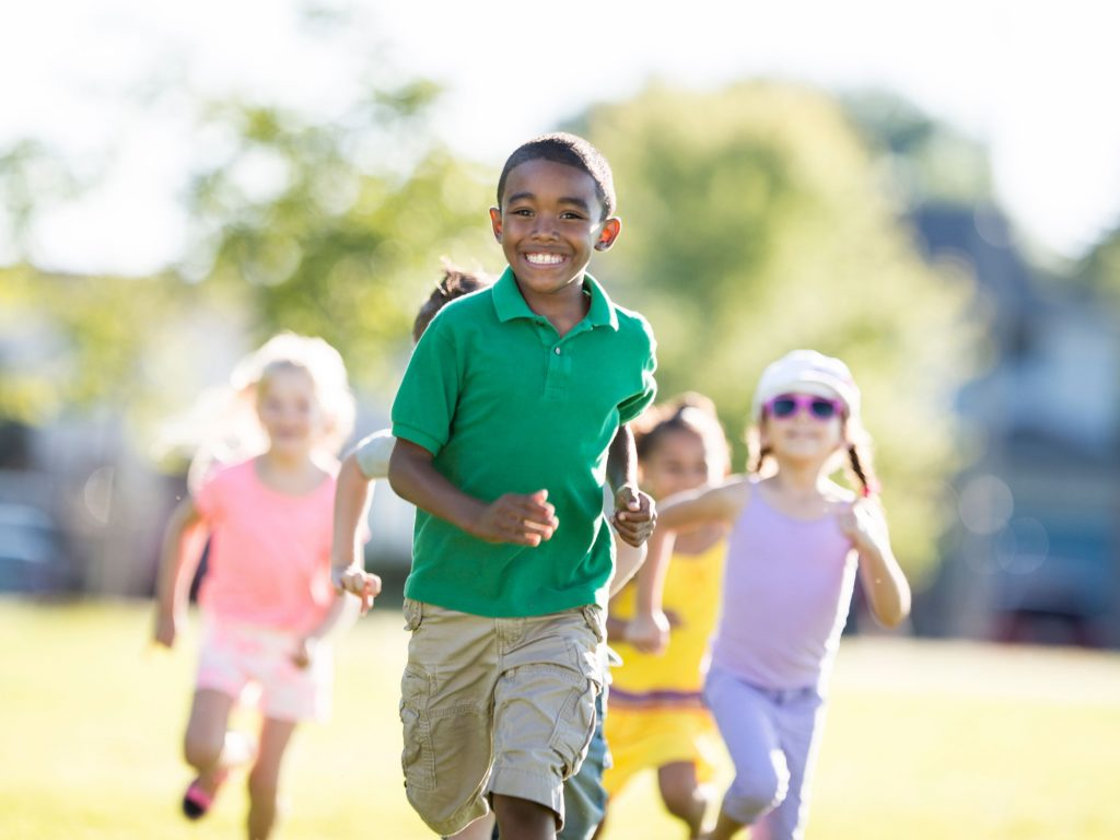 Several children running to find homebase in order to be safe during the game Ollie Ollie Oxen Free.