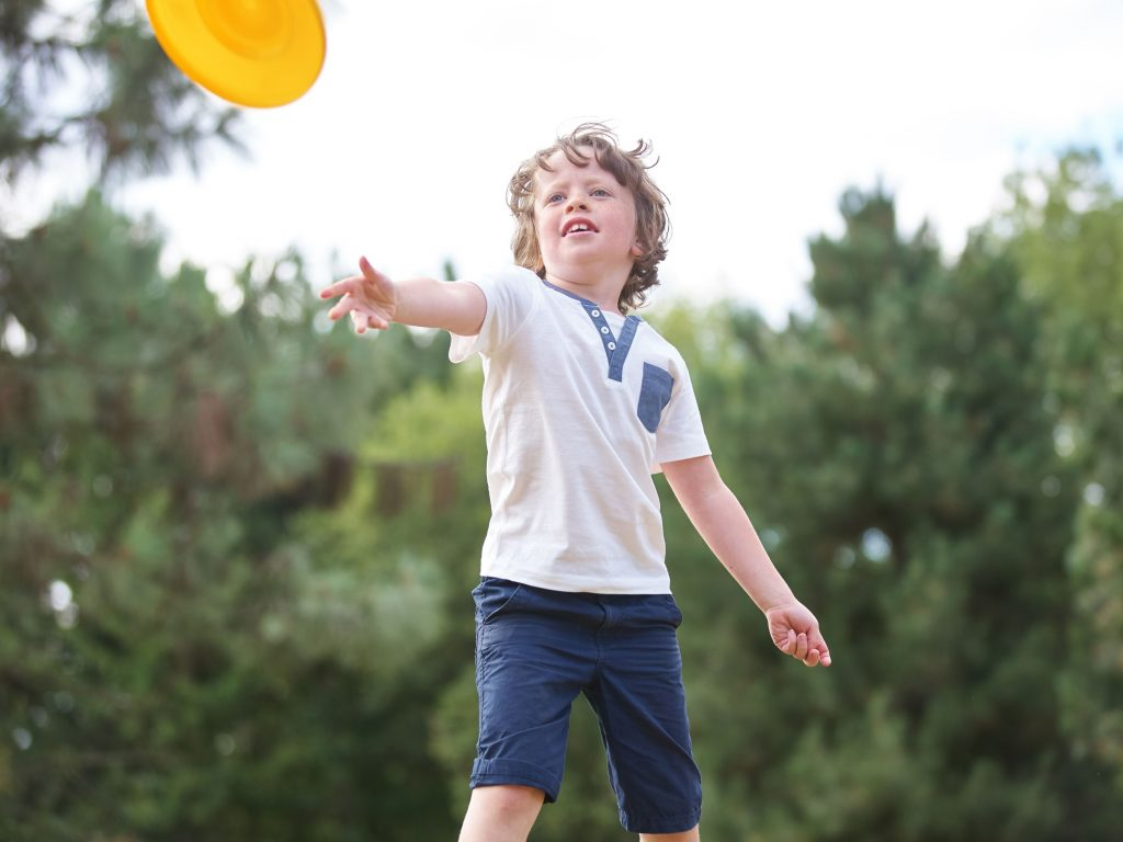 A young boy throwing a frisbee during an ultimate frisbee game in his backyard.