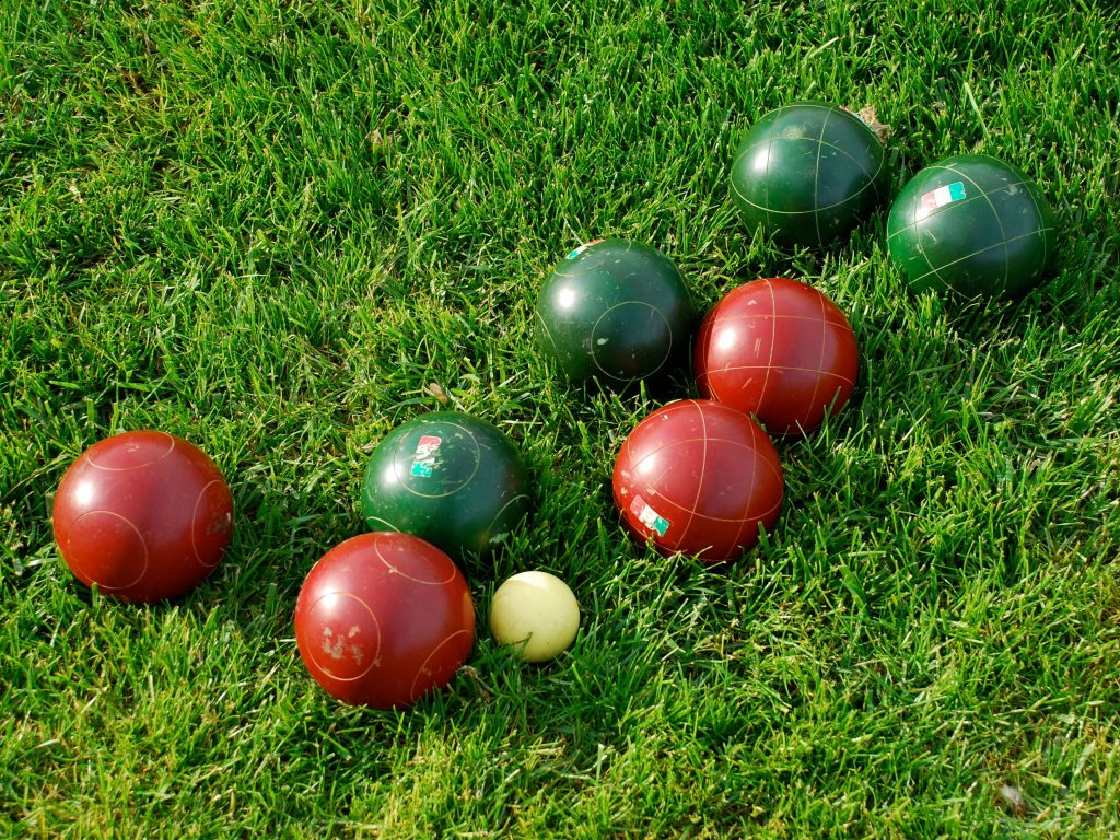 A complete bocce ball set sitting on grass waiting for kids to play.