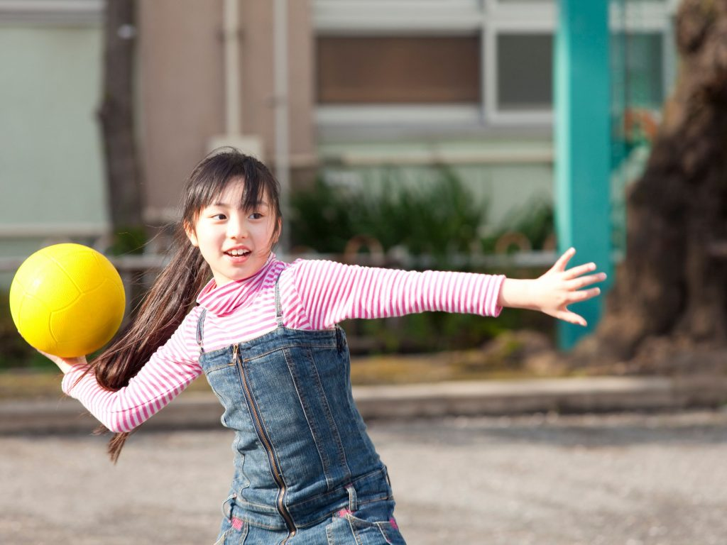 A girl throwing a yellow ball at her opponents during a friendly game of dodgeball in her backyard.