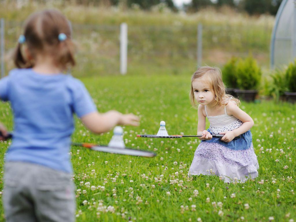 Two young girls playing badminton in a backyard.