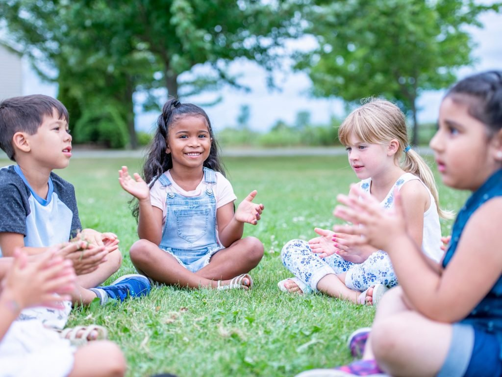Four children sitting in a circle while playing one of the most fun backyard games for kids: Drip, Drip, Drop.